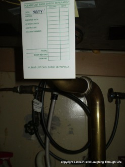 The pipes under my sink, with a bank deposit slip taped to the top