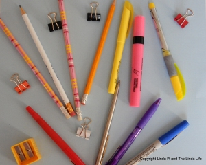 pens-pencils-clips-and-sharpener-on-blue-background